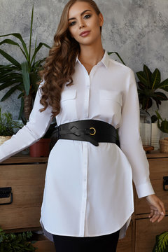 Medium full shot of a young European lady dressed in a black skirt, a white buttoned tunic shirt with pockets and a wide black leather belt with a bronze buckle and a thin leather strap tied