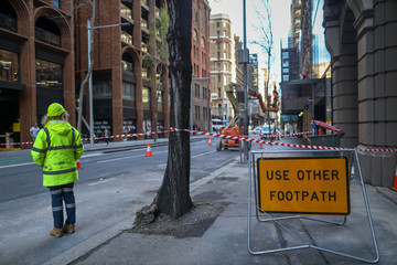 Use other footpath traffic warning sign barrier applying on busy street downtown on pedestrian footpath, road under construction with defocused traffic controller on side road worker at the background