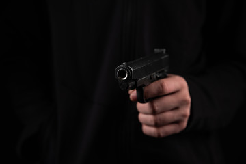 Gun in hand on black background. The threat of a firearm during a robbery on a dark street. Assault with a semiautomatic weapon.