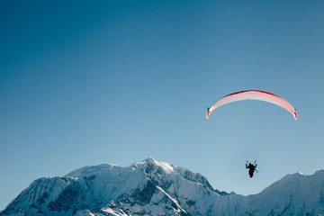 Paraglider silhouette in French Alps.