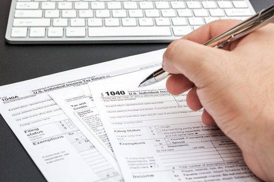 Man's hand filling tax form at workplace.