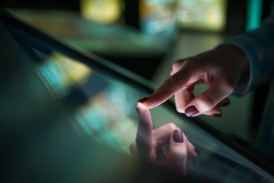 Woman using interactive touchscreen display of electronic multimedia kiosk at modern museum or exhibition. Education, learning and technology concept