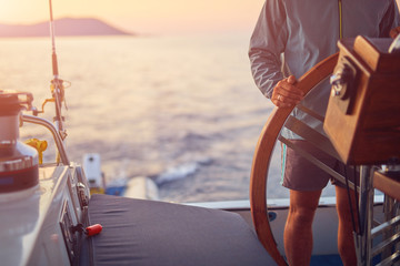 Sailor using wheel to steer rudder on a sailing boat.