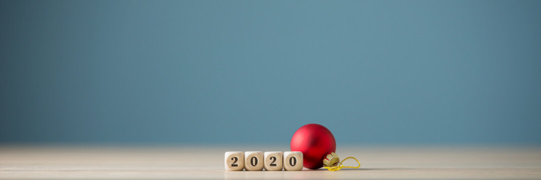 2020 sign on wooden dices with simple red holiday bauble next to it