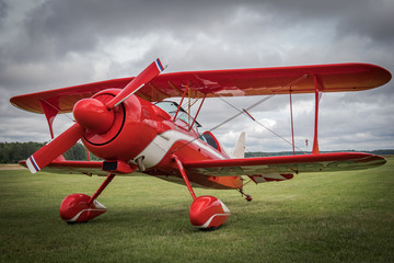 Beautiful red vintage airplane standing on the green grass near the airport field. Pitts Special Biplane
