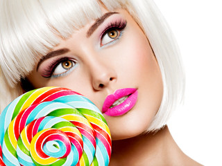 Closeup Face of a sexy girl with pink lips and multicolor sweet candy.