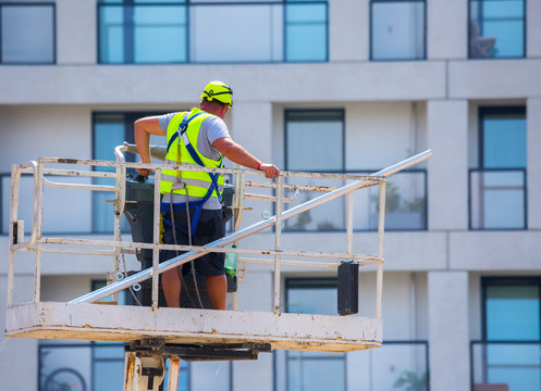 Professional installation work on a construction building site. Assemblers perform high-altitude installation works on the telescopic  boom lifts platforms. Installation of beams.