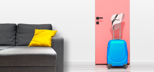 Blue suitcase with hat, near the sofa in the hallway. Travel concept