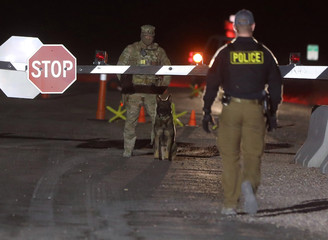 Military personnel with dogs guard a gate to Area 51 as an influx of tourists responding to a call to 'storm' Area 51, a secretive U.S. military base believed by UFO enthusiasts to hold government secrets about extra-terrestrials, is expected in Rachel