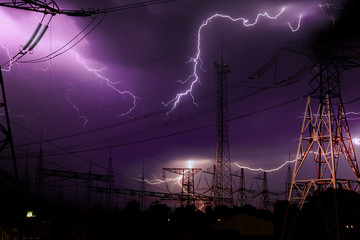 Fototapeta high voltage electrical substation illuminated by lightning flashes during an impending storm at night obraz