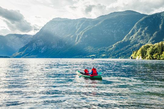 Couple paddling a kayak. Wonderful summer scene of Bohinj lake, Triglav National park. Sunny morning view of Julian Alps, Slovenia. Concept for adventure, travel, action, lifestyle.