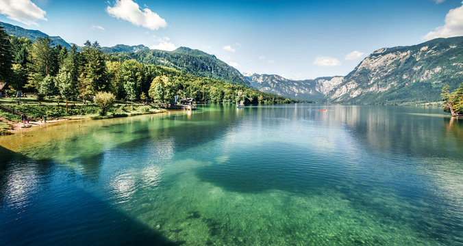 First sunlight glowing surface of Bohinj lake. Spectacular summer panorama of Triglav national park. Great morning view of Julian Alps, Slovenia, Europe. Traveling concept background.