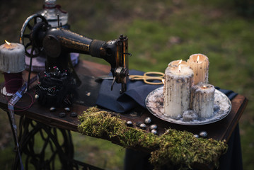 an old sewing machine with moss and burning candles outdoors