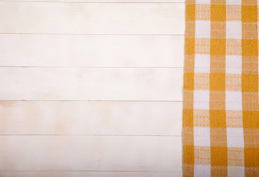 Linen yellow napkin lies on a white wooden background. Horizontally. View from above. Copy cpaes