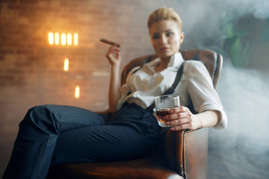 Woman sitting in chair with whiskey and cigar