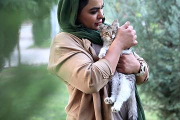 Iranian bodybuilder Sharareh Nobahari holds a cat at a park in Tehran