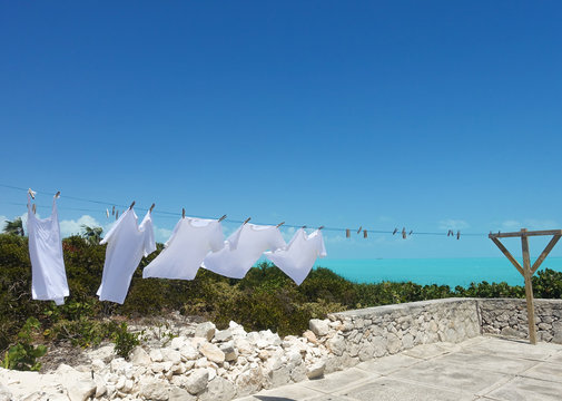 White shirts dry on a clothesline next to the Caribbean Sea in the Turks and Caicos islands