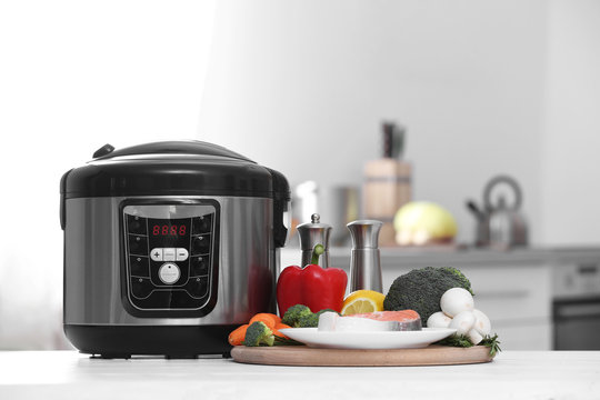 Modern multi cooker and products on table in kitchen