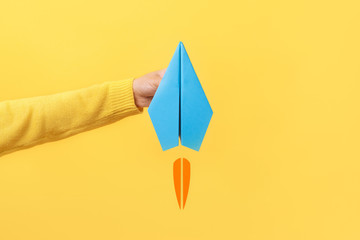 Wall Mural - hand holding paper plane over yellow background