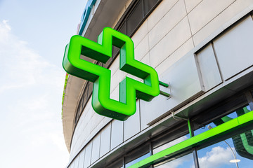 Close-up of green cross - sign of pharmacy on glass building