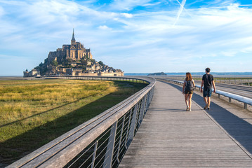 A couple heads to Mont Saint Michael on the only access road. On foot it is one of the options allowed for access, perhaps the most beautiful because it is enjoying a spectacular landscape.