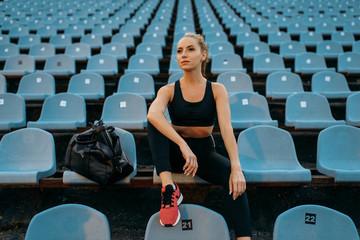 Female jogger in sportswear sitting on tribune