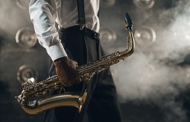 Black jazz musician with saxophone on the stage Fotomurales