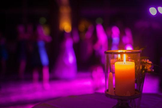 Kerze auf Hochzeitsfeier, Tanzfläche im Hintergrund