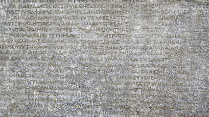 Ancient Greek writing on rock for background. Antique inscription carved on stone. Old script text close-up. Gray wall with historic letters. Vintage texture with words from past civilization.