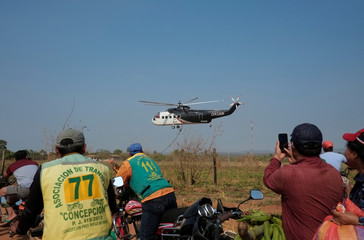 People look and take pictures of the helicopter equipped to fight against fires in Concepcion