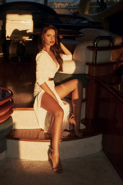 Stylish glamorous elegant woman with long legs and straight brown hair sitting at stairs at luxury yacht. Evening lightning. Tanned fashionable girl. Full length portrait