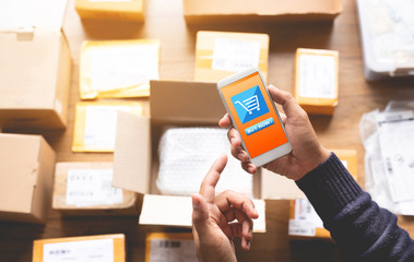 Online shopping concepts with youngman using smartphone for payment his order on a lot of product package box.