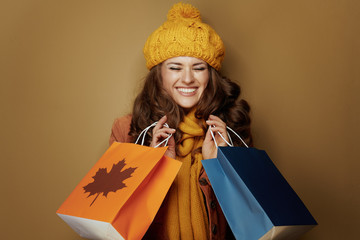 woman with autumn shopping bags isolated on beige background
