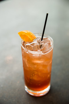 Orange color cocktail over cement surface.