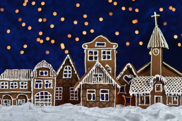 home made gingerbread town with church and bokeh sky out of blue velvet and christmas lights as advent decoration for the family