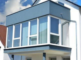 Vorgebaute Wintergarten-Balkon-Kombination mit dreiseitiger Verglasung an einem Wohnhaus