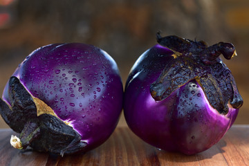 Two purple round eggplants with drops of water lie on a table in front of brown background in summer on Sicily
