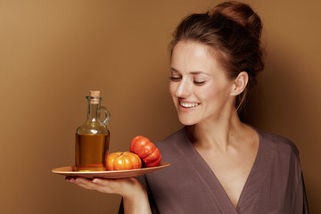 middle age woman looking at pumpkin oil on brown background
