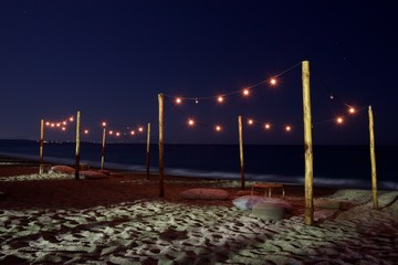 Long exposure night photo of large cushions and pouf at empty beach at summer, under light bulbs...