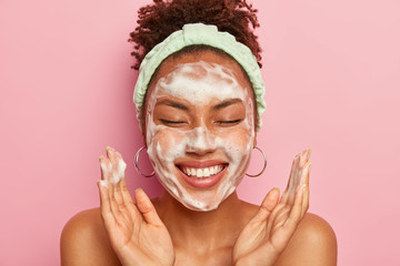 Image of happy ethnic woman raises palms over face, keeps eyes closed, shows white teeth, uses cleansing foam for skin care, gets real pleasure, wears headband and earrings, stands topless alone