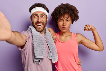 Happy diverse woman and man take selfie, dressed in casual clothes, stand closely to each other, go in for sport, stand against purple background. People, wellness, fitness and workout concept Wall mural