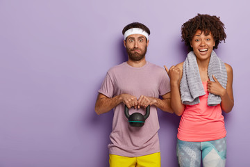 Photo of happy young African American woman with towel on shoulders points at husband who has surprised expression, lifts weight, blows cheeks from tiredness, stand together over violet wall