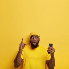 Photo of surprised wondered black man in glasses points index finger above, surfes internet page and sends picture, keeps mouth widely opened, holds modern cellular, isolated on yellow background.
