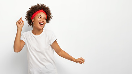 Horizontal shot of happy upbeat African American woman raises arms, looks away with delighted expression, dressed in casual wear, isolated over white background, blank space for your promotion