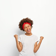 Photo of happy delighted Afro girl clenches fists, feels triumph, rejoices victory, keeps eyes shut, smiles broadly, wears white t shirt, stands indoor. Yes, I did it successfully. People, high spirit