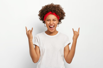 Photo of energetic young African American woman makes rock n roll gesture, enjoys cool music, smirks face, dressed in casual wear, poses against white background. People, body language concept