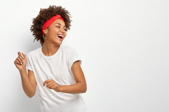 Sideways shot of happy positive African American woman looks gladfully away, dances in rhythm of music, keeps head turned away, dressed in casual clothes, isolated on white background. Happiness