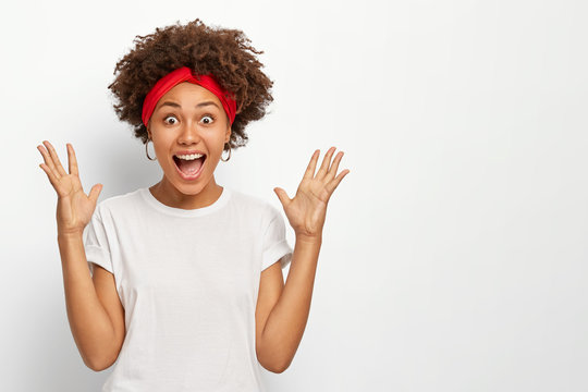 Photo of overemotive dark skinned African American woman raises palms, keeps mouth widely opened, reacts on something awesome, dresed in casual wear, isolated on white background. Wow, how nice!