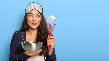 Happy busy Asian housewife whisks cream in bowl, wears sleep mask and pyjamas, cooks early in morning after aweking, poses against blue background. Woman makes homemade cake. Cooking concept