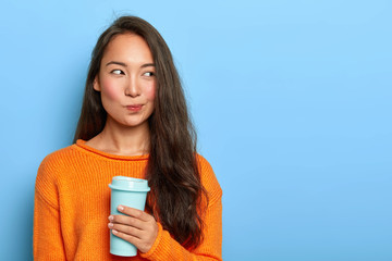 Photo of pensive brunette woman purses lips, looks thoughtfully aside, holds takeout coffee, makes decision in mind, plans her day, wears orange jumper, stands over blue wall. Asian girl with beverage Fotomurales